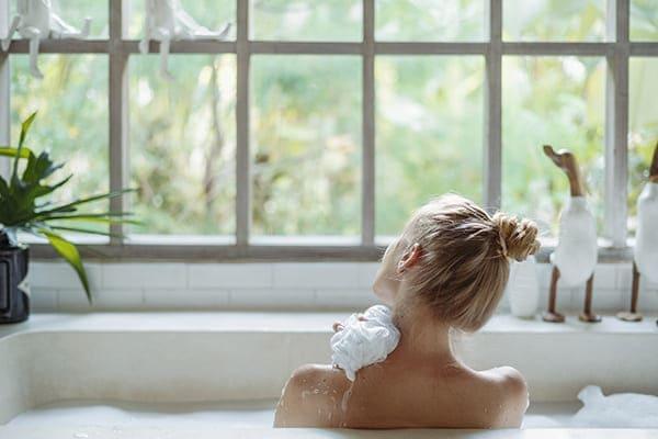 Frau sitzt in der Badewann und schaut aus dem Fenster.