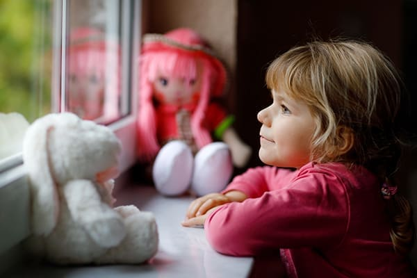 Mädchen schaut lächelnd aus dem Fenster.