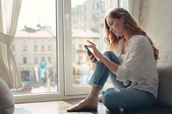 Frau sitz vor Fensterfront