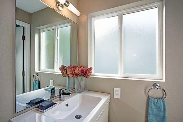 Badezimmer mit Waschbecken und Fensterornamentglas