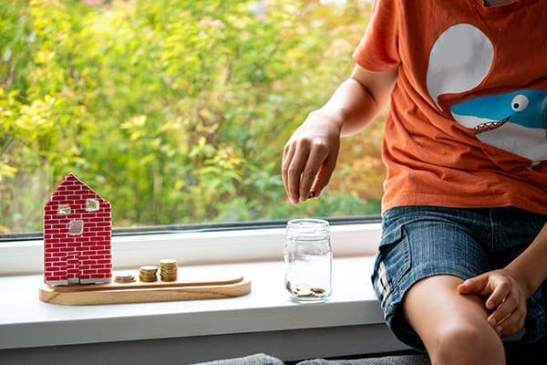 Kind mit Geld und kleinem Haus auf der Fensterbank.