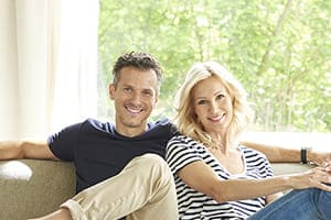 Glückliches Paar sitzt auf dem Sofa. Im Hintergrund große Fensterfronten mit Vorhang auf der Seite.