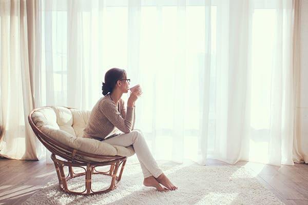 Frau sitzt mit Tasse vor Fenstefront.