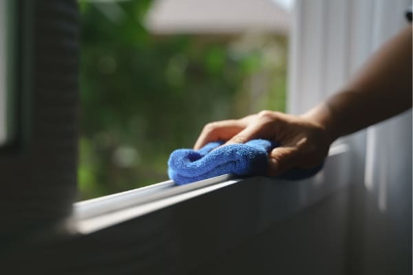 Person wischt mit blauem Lappen das Kunststofffenster sauber.