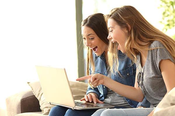 Zwei junge Frauen sitzen lachend und sehr glücklich vor dem Laptop.