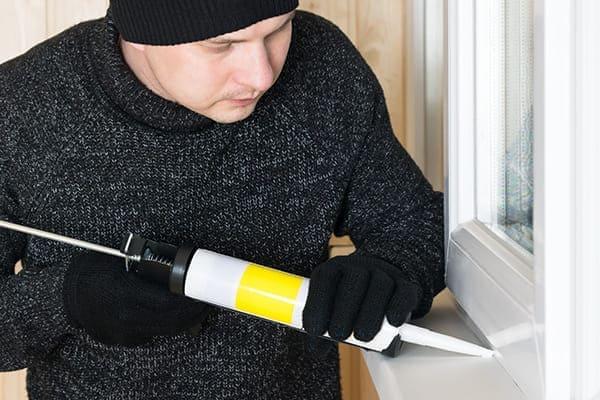 Monteur dichtet Fenster mit Acrylat ab.
