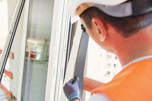 Monteur klebt auf Fensterrahmen ein RAL-Band.