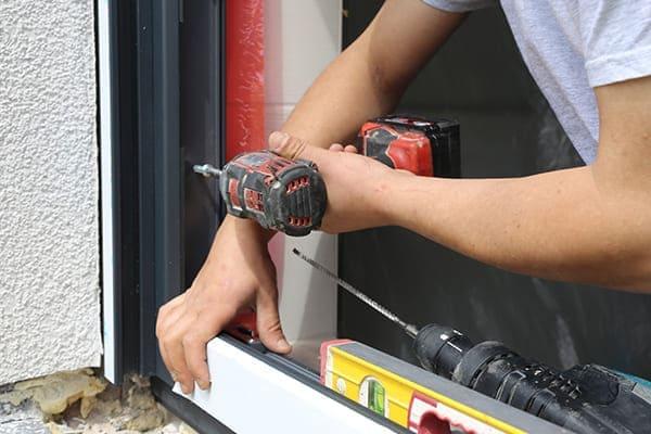 Mann schraubt Fenster in Mauerwerk fest.