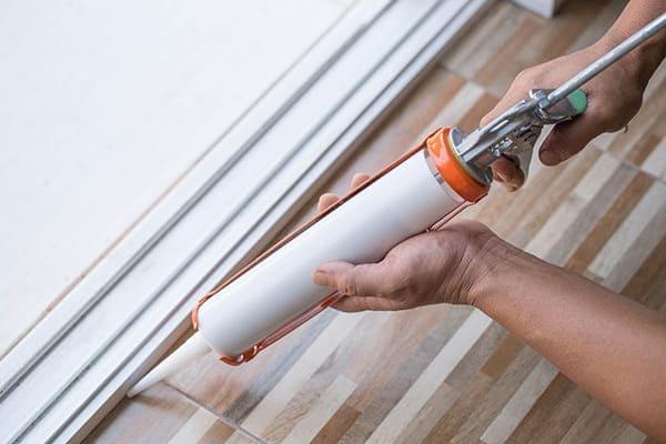 Monteur spritzt mit Silikon die Innenfuge des Kunststofffensters aus.