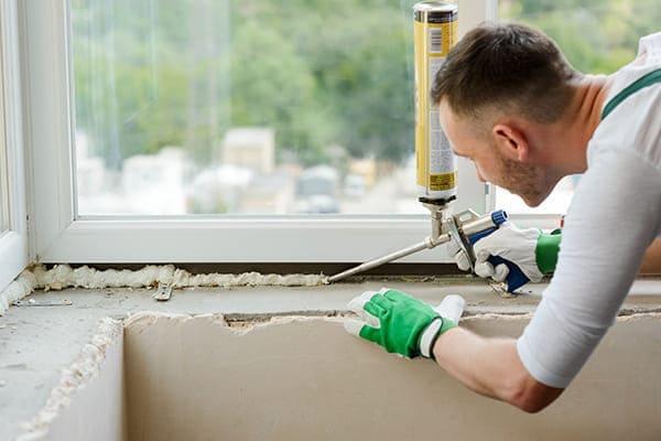 Monteur spritzt PU-Schaum in die Fensterfuge.