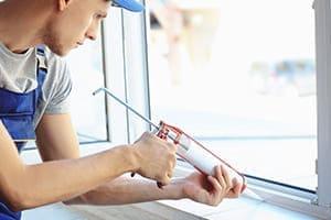 Monteur spritzt Fensterfuge innen aus.