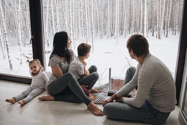 Familie sitzt vor braunen Fenster draußen Winterlandschaft