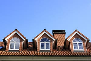 Drei Rundbogengieblfenster mit weißen Sprossen.