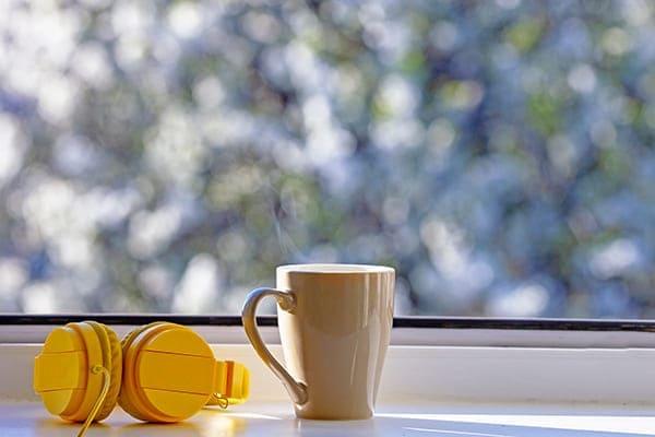 Kopfhörer und Tasse sehen vor Fensterscheibe.