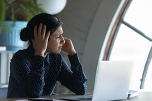 Frau sitzt am Schreibtisch mit Leptop und hält sich die Ohren zu. Im Hintergrund großes Fenster.