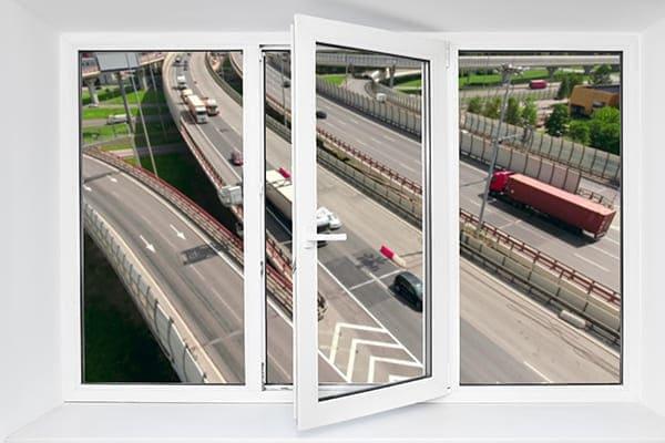 Weißes Fenster im Hintergrund ist eine stark befahrene Autobahn zu sehen.
