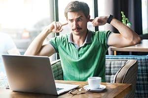 Mann sitzt in Cafe und hält sich die Ohren zu und versucht mit seinem Laptop zu arbeiten.
