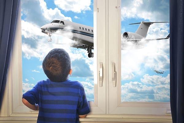 Kleiner Junge steht vor dem Fenster und schaut dem Flugzeug am Himmel zu.