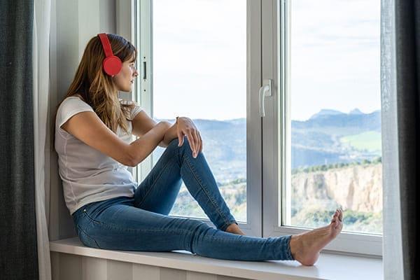 Junge Frau sitz mit Kopfhörern vor Fenster und hört Musik.