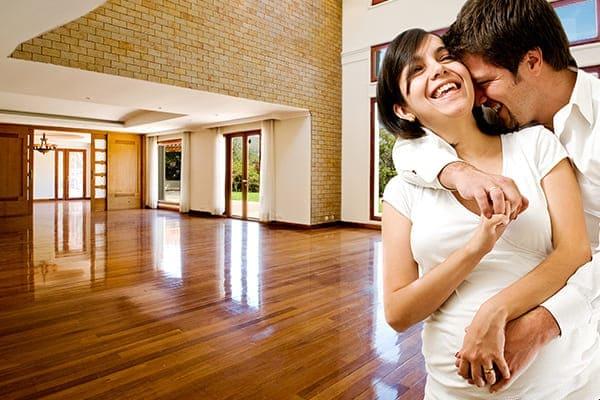 Junges glückliches Paar im neuen Haus mit Schallschutzfenstern.