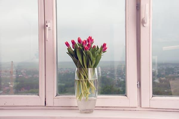Altes Holzfenster mit Blumenvase und Blumen auf der Fensterbank.