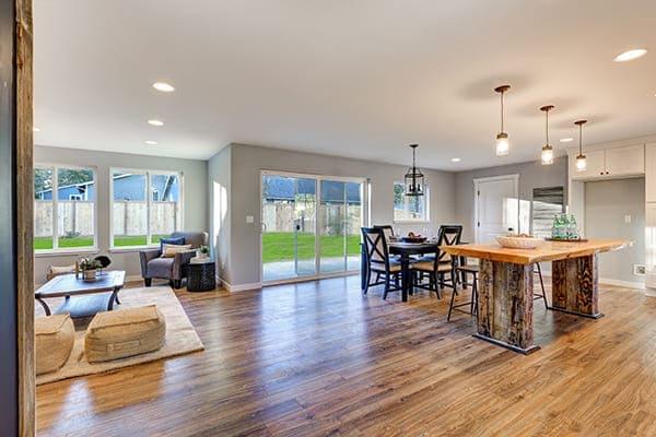 Die offene Inneneinrichtung mit poliertem Holzfußboden Esstisch und Schiebetüren auf einen eingezäunten Hinterhof.