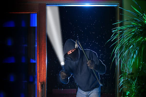 Einbrecher steht mit Taschenlampe und Brecheisen vor einer großen Schiebetür.