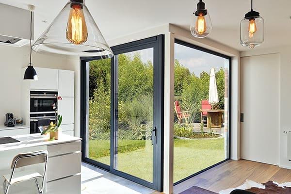 Küche mit großem Schiebefenster als PAS-Tür gezeigt in Anthrazitgrau.