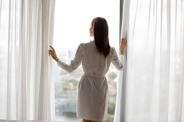 Frau steht entspannt mit Bademantel vor dem großem Schiebefenster.
