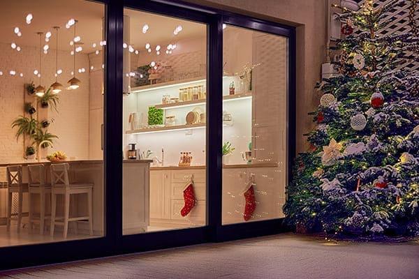 gemütliches Apartment mit Schiebetüren und verziertem Weihnachtsbaum auf der Terrasse.