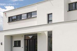 Neubau von außen geshen in weiß mit Anthrazitfarbenen Fenstern.