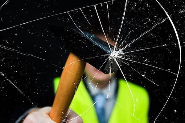 Mann mit gelber Weste im Hintergrund zerschlägt Glasscheibe mit einem Hammer.