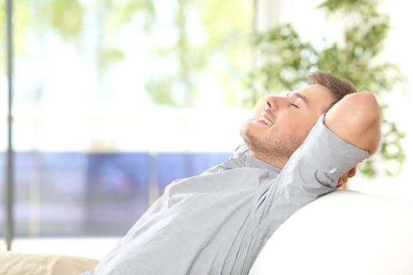 Mann entspannt auf dem Sofa Fenster im Hintergrund