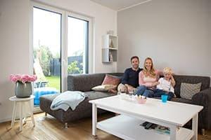 Familie sitzt auf Couch im Wohnzimmer im Hintergrund 2-flügelige Balkontür.