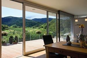 Wohnzimmer von innen mit großem Terrassenfenster nach draußen.