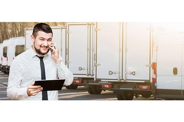 Manager mit digitalem Tablet und Telefon im Hintergrund Lkw's.
