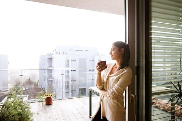 Frau leht sich an geöffneter Schiebetür an und trink einen Kaffee.