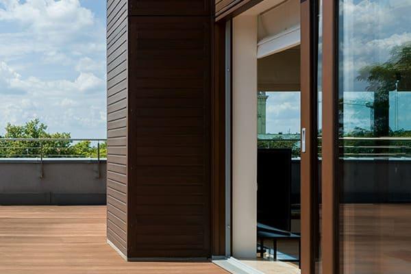 Panorama auf der großen Terrasse mit brauner Terrassen Schiebetür.