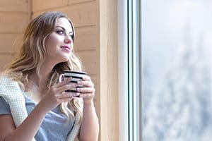 Frau sitz auf Sofa trink Tee und schaut aus dem Fenster.