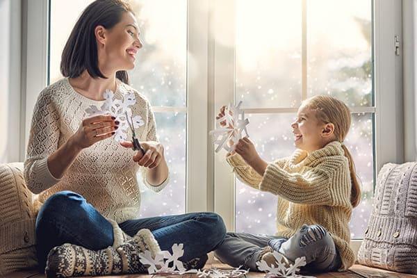 Mutter und Kind sitzen vorm Fenster draußen ist eine Winterlandschaft zu sehen.