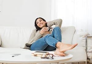 Junge lächelnde Frau, die auf dem Sofa sitzt und beim Trinken heißen Tees aufsieht.