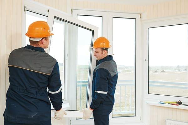 Zwei Montuere hängen Fensterflügel ein.