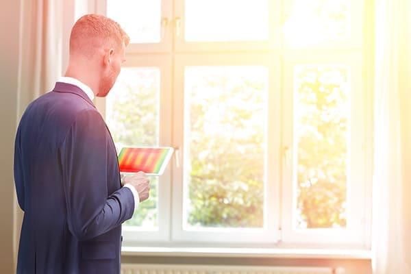 Geschäftsmann steht für Fenster mit Wärmebildkamera auf seinem Talett