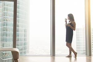Frau steht im Hochhaus vor großer Fensterfront und sieht nach draußen und trinkt dabei einen heißen Kaffee.