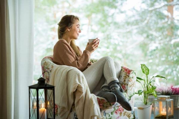 Frau sitzt mit Tee im Sessel an Fenster mit Waermeschutzverglasung inklusive.