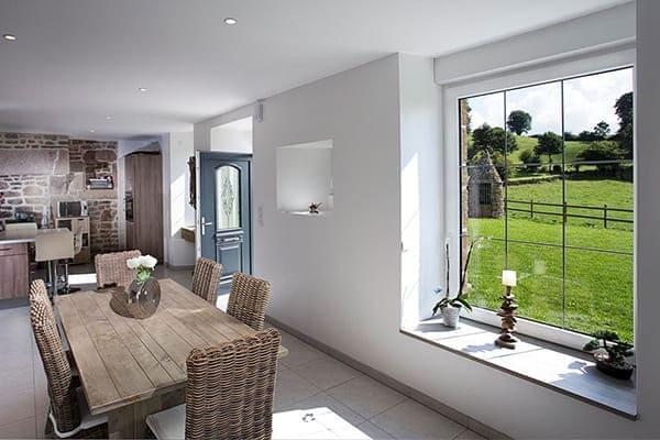 Heller Raum mit großem Sprossenfenstern und geöffneter Haustür in anthrazit