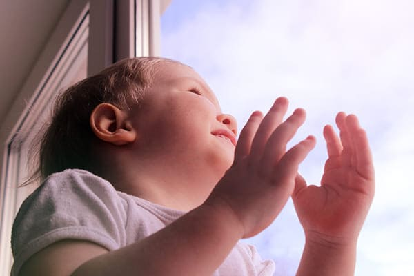 Kind sitzt vor Fenster.