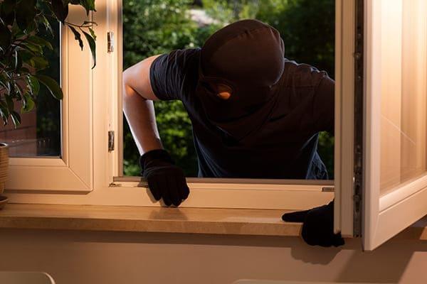 Einbrecher will über offenes Zweiflügelfenster reinspringen.