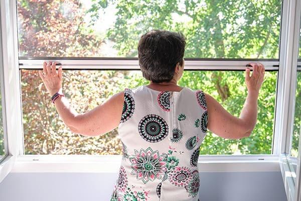 Frau zieht Insektenschutzrollo nach unten bei einem Zweiflügeligem Fenster.