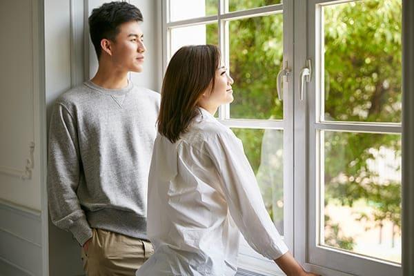 Paar steht vor Zweiflügelfenster und schaut nach draußen.